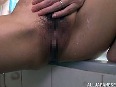 Horny Japanese MILF takes a bath. She shows her nude body under the running water and then start to pour water on her pussy.