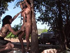 It's a lesbian outdoors femdom session with bondage and toying action taking place somewhere on an island.