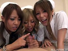 Three Japanese nurses play with a patient's cock in a hospital