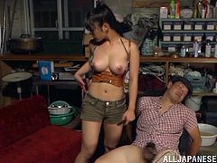 Nasty Japanese girl in a miniskirt has fun with tied up dude in the shed. She takes his dick in her hands and give a handjob passionately.