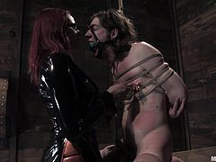 Miss Adams has the know how to treat a man and a girl right. She tied up Kade and put the slim cutie Riley in a cage under Kade. Because she's a skilled mistress she takes care of both at the same time. As that bitch sits quietly in the dawg house Miss Adams spanks and tortures Kade.