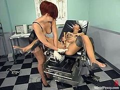 Roxy Jezel and Sonya are playing BDSM games in a doctor's office. Sonya binds Roxy up and attaches wires to her pussy and then fucks her pink cave with a dildo.