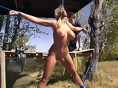 Sexy blonde with nice boobs and ass gets tied up and gagged outdoors. A guy whips her boobs and ass painfully.