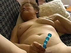 Sassy grandma takes off her dirty undies displaying her saggy tits. Old tramp rubs her loose hairy snatch and fondles her pussy lips with vaginal beads.