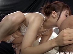 Charming Japanese girl Yui Ooba wearing a bra and panties kneels in front of some guy and begins to suck his schlong. Then she licks the man's asshole and gets loads of cum on her tits.
