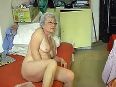Skanky pale bodied granny takes her clothes and lies in bed. Old bitch spreads her legs wide open and starts fucking her loose snapper with dildo.