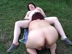 Two BBWs take their clothes off outdoors. They lie down on the ground and have wild lesbian sex. These crazy chicks lick each others pussies with great passion and pleasure.