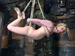 Sexy blonde girl gets gagged and tied up by a weird couple. This blonde gets tortured by the man in military uniform and the bald chick.