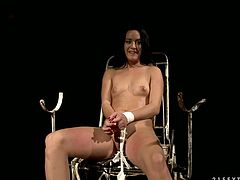 Adorable black haired slave girl sits on metal chair all naked with her arms bounded. Mean hory mistress slaps her face and rubs young babe's big tits.