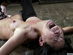 Kinky Asian girl lies on the floor being chained. Then her master fixes clothespins to her nipples. Surely, then she gets toyed.