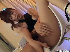 This sexy Japanese babe plays with her pussy while sitting on a chair. She shows her pink hole when she shoves a vibrator in.