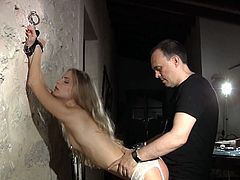 Cayenne Klein is cuffed to a wall by her master. She's wearing sexy stockings and suspenders, which even for him are irresistible. He bangs her from behind and ties her up again.