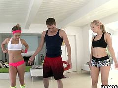 After warming up on the gym mat, these two horny young babes give their fitness instructor a double blowjob and switch turns riding his cock.