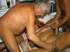 Fat suntanned granny gets naked in bed and shows off her bearded clam. Two old guys lick her wet hairy cunt and get their flabby dicks sucked.