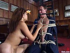 Annie Cruz binds submissive stud Wild Bill indoors and pulls him by the balls. Then she fucks his ass with a strapon and makes him watch her playing with her cunt.