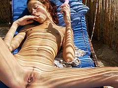 sexy, petite Natasha strips naked and drives her toy deep into her tight pussy while relaxing on her lounge bed out on her deck.