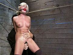 Submissive blonde chick gets gagged and tied up. Then a guy toys her shaved pussy with a vibrator. This chick really enjoys.