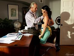 Katie likes older men like Tom Byron. She lets him fucks her like a crazy bitch. He unbuttons his shirt and she pulls out her boobs. She hikes up her skirt and he eats her pussy on the desk in his office.