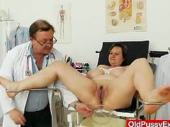 Voluptuous mommy with big juicy jugs is standing naked in front of perverted Doc. He grabs her boobs in both hands kneading them actively. Later he measures her body.