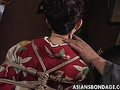 The sensual brunette geisha is all tied up and she awaits her punishment in the dark. The obedient bitch soon receives a visit from this guy that wants to satisfy his needs with her. He gropes her boobs and taunts her, making the whore horny as hell. Such an obedient women is tied up unnecessary, what is he up to?