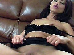 Stunning brunette girl in stockings and lingerie lies on a sofa. She licks her toes and then starts to finger her shaved pussy.