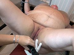 Super fat SSBBW granny lies on her back all naked bounded by her arms and legs. Kinky mistress attaches clamps to that dirty pussy and fucks it with big dildo.