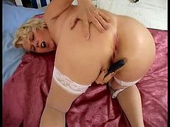 Click to watch this mature blonde, with big jugs wearing white lingerie, while she touches herself over a nice bed and plays with dirty toys.