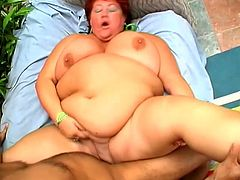 Redhead BBW Agnes is getting naughty with some horny dude indoors. Agnes titfucks the man's boner and then welcomes it in the folds of her fat twat.