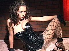 Crissy Moran poses in her leather costume while undulating and feeling her forms