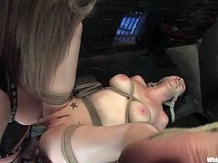Maitresse Madeline restrains hot brunette Natalie Minx in a basement and plays BDSM games with her. Maitresse whips her slave with a lash and then destroys her coochie with a strapon.
