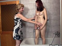 Slutty redhead Nikola takes a long, relaxing shower. She makes sure her pussy is getting clean, too clean! The slut enjoys herself and loves how the water jet from the shower feels on her snatch. Soon, she receives some company as the mom of her bf, a blonde comes inside the shower to help her masturbate.