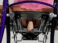 Woman uses a diletto sex chair.