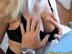 Have fun watching this blonde MILF, with giant boobs wearing black lingerie, while she goes hardcore with a naughty fellow over a nice bed.