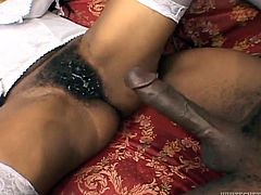 Ebony girl in stockings and a corset gets her hairy pussy drilled by Black dude. Later on she lies down on a sofa and gets ass fucked.