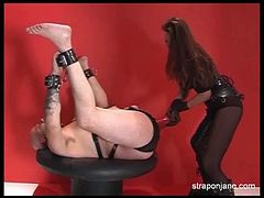 Jane is not a permissive mistress. She ties up her slave's hands to his feet and inserts a huge, black strapon inside his brown hole. Next she switches to a dildo.