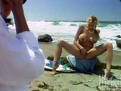 Curvaceous Stormy Daniels poses for the camera on the beach. After some time she takes a bikini off and starts to rub her shaved pussy.