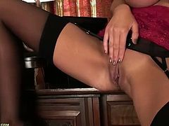 Leigh Darby is a British cougar with a sexy accent, huge boobs and long legs. She gets off after she strips and she sits on the floor pleasuring her pussy.