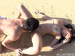 Playful Japanese girl lies down on sand and gets her vagina licked. Later on she gives a handjob and a blowjob. This babe gets fucked on beach as she likes.