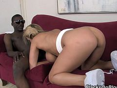 White babe with a pretty face and fake tits gives a blowjob to big cocked Black guy. Then Alanah lies down on a sofa and takes rough pussy pounding.