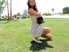 Kinky brown-haired chick Jody wearing a sundress is having fun outdoors. She pulls her dress up and demonstrates her butt and shaved cunt for the camera.