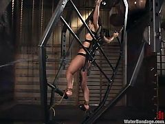 This young brunette gets locked up in a huge contraption by her mistress. she is strapped down with leather straps. Then the mistress walks away. Where is she going? She's going to get the hose and sprays this naive girl with cold water.