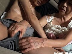 This Japanese lady sits in the back of her car with her young friend and she lets him suck on her nipples. She pulls out his cock and likes how big it is. She does a good job of jerking him off because she has years of experience.