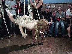 This dirty little slut is locked in a cage so she can be mocked and humiliated. She is tied up with ropes and has her tits squeezed by the mistress. She is lifted up to the ceiling so all the guests can look at her naked body.