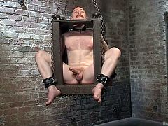 The male whore stays hanged in a bondage box when his executor steps in firmly. He grabs his shaved penis and begins to rub it nice and hard. The male slut moans and wants to cum but what will happen if he cum stains his executor's hand? Stay with him and find out!
