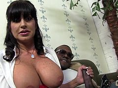A huge breasted MILF strokes a big black cock in a backstage vid
