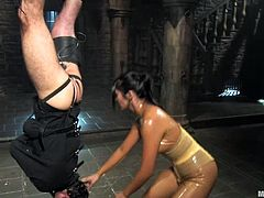 Dominatrix Mika Tan is glistening while she is covered in oil. Her slave can't even scream as he is being whipped because there's a mask on his face. She takes the mask off so her can beg and get a breath of air.