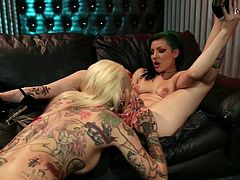 These horny tattooed babes are sharing a big strapon together