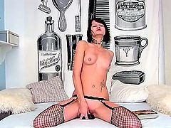 Tattooed princess Nova Black with pierced nipples curves on a bed in fishnet stockings and drills vagina with a toy
