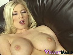 Sizzling big-breasted blonde milf Michelle B is having fun in the living room. She sits on a sofa with her legs moved wide apart and entertains herself by finger-fucking her shaved snatch.