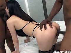 A gorgeous Japanese woman has an interracial threesome sex. This chick in fishnets and sexy lingerie gives a blowjob to one dude and gets fucked from behind by the other one.